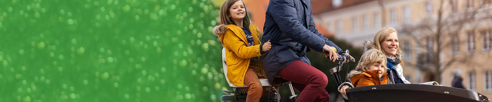 Gezin fietst met de bakfiets langs de kerstbomen