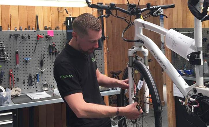 Fiets! werknemer herstelt Flyer e-bike in de werkplaats
